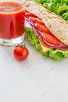 panino estivo con prosciutto, formaggio, insalata e pomodori, cipolla, succo di frutta foto