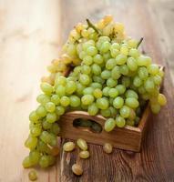 uva verde su un vassoio di legno foto