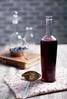 vecchia bottiglia di vino con aceto di bacche fatto in casa. foto