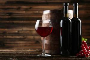 bicchiere di vino rosso con bottiglia e botte foto