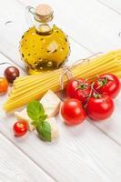 pasta, pomodori, basilico sul tavolo di legno foto