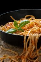 linguine al basilico e salsa rossa in padella di ferro foto