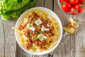 pasta alla bolognese in ciotola bianca con insalata e pomodori