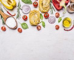 ingredienti che cucinano il bordo rustico di vista superiore del fondo della pasta vegetariana foto