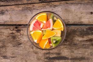macedonia di frutta fresca in una ciotola di vetro. foto