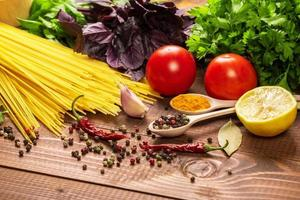 pasta cruda, verdure, basilico e spezie sul tavolo di legno foto