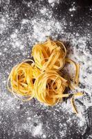 tagliatelle di pasta cruda sul tavolo foto