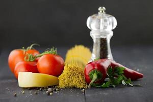 ingredienti italiani: spaghetti, spezie, pomodori, peperoncino su fondo in legno
