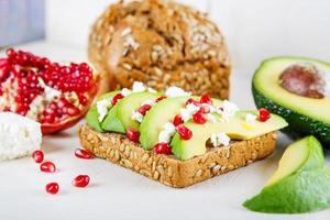 avocado con feta, melograno su sandwich di pane con semi di girasole foto