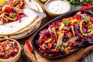 fajitas di maiale con cipolle e pepe colorato, servite con tortilla