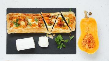 crostata con zucca, formaggio di capra, olive sul tagliere di pietra foto