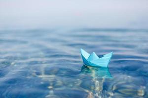 barca di carta a vela sulla superficie dell'acqua blu foto