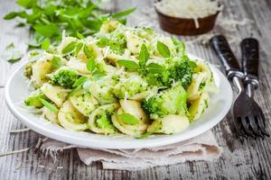 orecchiette di pasta fatta in casa con broccoli, parmigiano e basilico foto