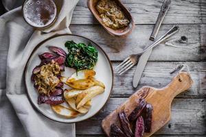 bistecca con patate al forno e insalata verde su fondo in legno foto