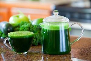 tazza di vetro di succo di verdura verde sul bancone della cucina foto