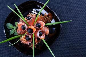 pesce rosso sul piatto con olive e spezie. salmone salato foto