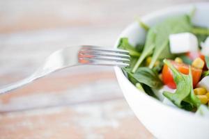 Chiuda in su della ciotola di insalata di verdure foto
