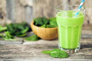succo di frullato verde sul tavolo di legno con spinaci foto