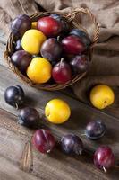 Merce nel carrello fresca delle prugne sul bordo di legno foto