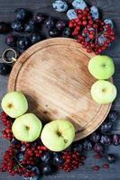 vecchia tavola, prugne, viburno e mele sullo sfondo foto