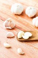 aglio organico intero e chiodi di garofano sui precedenti di legno foto