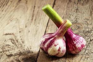 lampadine organiche fresche dell'aglio sulla vecchia tavola di legno, fuoco selettivo foto