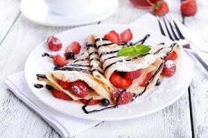 deliziose frittelle con frutti di bosco sul primo piano tavolo foto