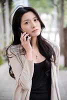 ragazza asiatica che per mezzo di un telefono cellulare foto
