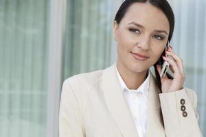 telefono cellulare di risposta della bella donna di affari all'aperto foto