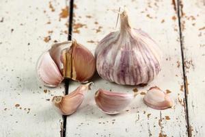 bulbi d'aglio e chiodi di garofano sul tavolo della plancia di vernice scrostata foto