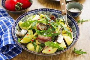 insalata con patate, acciughe e rucola. foto