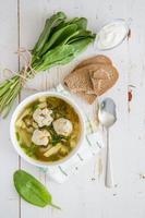 zuppa di acetosa con polpette di carne, pane, panna acida, tovagliolo a quadri foto