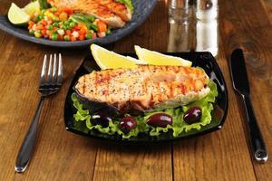 gustoso salmone alla griglia con limone e verdure, sul tavolo di legno foto