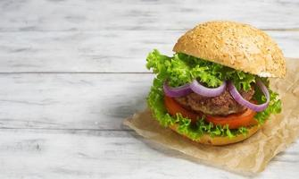 hamburger con cotoletta di manzo, lattuga, cipolle e pomodoro foto