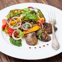 Insalata tiepida con fegato di pollo, verdure e lattuga foto
