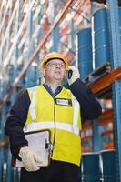 lavoratore che utilizza telefono cellulare nel magazzino foto
