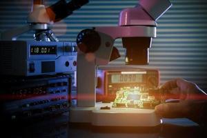controllare il dispositivo microelettronico in un microscopio da laboratorio foto