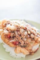 carne di maiale fritta con salsa di pomodoro topping su uovo fritto foto