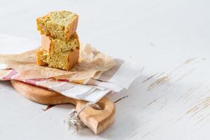 quadrati di pane di mais su carta da forno, tavola di legno foto