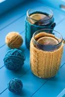 due tazze di tè in maglioni lavorati a maglia gialli foto
