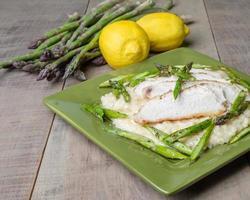 risotto agli asparagi con pollo sul piatto verde foto