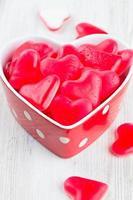 caramelle a forma di cuore in una ciotola su superficie di legno foto