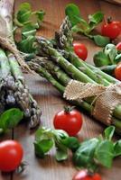 asparagi biologici su tavola di legno accompagnati
