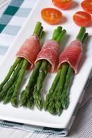 asparagi verdi con vista dall'alto verticale di prosciutto e pomodoro foto