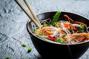 gamberi e verdure serviti con noodles