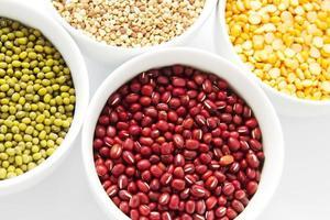 set di diversi fagioli e grano saraceno in ciotole bianche foto