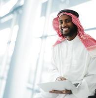 uomo d'affari arabo con tavoletta in ufficio foto