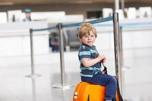 ragazzino andando in vacanza viaggio con la valigia in aeroporto foto