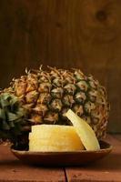 dessert ananas affettato su un piatto di legno foto