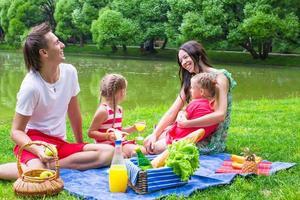 giovane famiglia felice che fa un picnic all'aperto vicino al lago foto